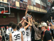 Union High School players and fans hoist Izaiah Vongnath after Vongnath cut down the net following Union's 61-60 victory over Skyview in Friday's 4A/3A GSHL district championship in boys basketball.
