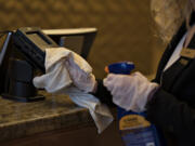 Guest service agent Libby Lusk keeps the credit card machines at the front desk disinfected at the Hilton Vancouver in 2020.