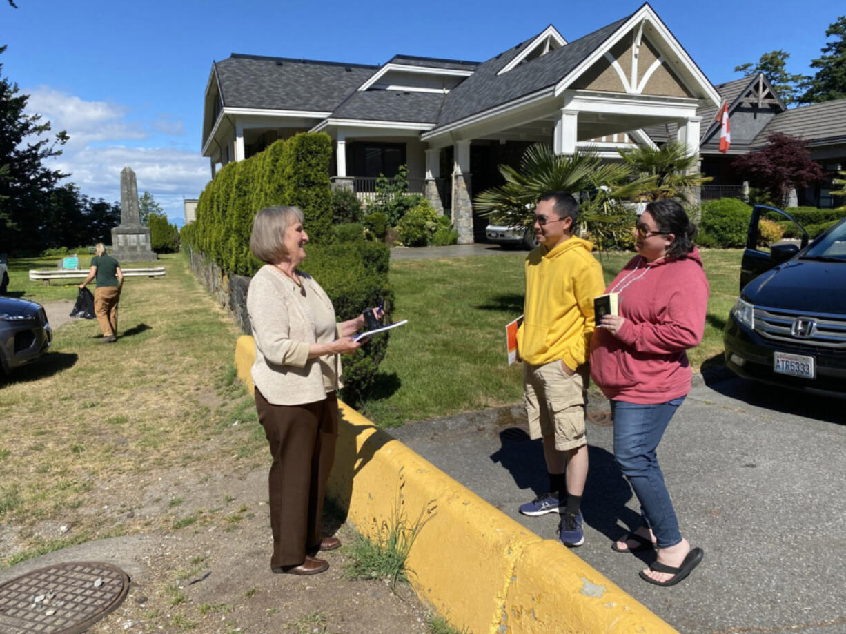 Notary public Julia Carlson, left, stands in Point Roberts, talking to Khue Le and his wife, Shelby, in Canada.