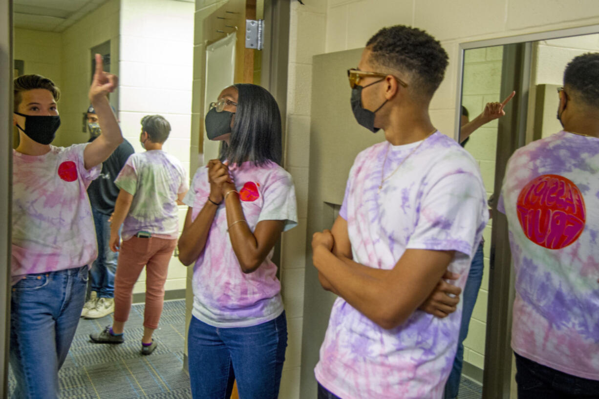 George Washington Carver High School humanities teacher Kit Bradley, from left, talks with seniors Amoya Donaldson and Caleb Autry at the school. Carver launched its own record label during the pandemic with students filling every role, from talent to executive producers.
