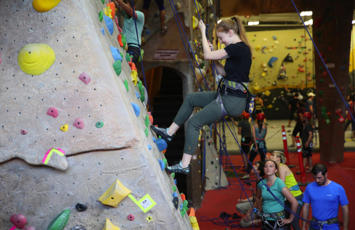 A climber tests a beginners wall, learning top-roping techniques during a Climbing 101 class at Stone Gardens in Seattle.