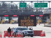 U.S. Customs officers stand beside a sign saying that the U.S. border is closed at the at Lansdowne, Ontario, on March 22, 2020.