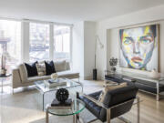 A bold piece of artwork with dominant accents of chartreuse serves as a focal point in this living room.