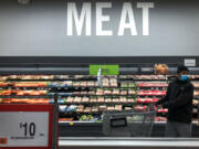 A man shops in the meat section at a grocery store April 28, 2020, in Washington. Inflation at the wholesale level jumped 1 percent in June, pushing price gains over the past 12 months up by a record 7.3 percent. The Labor Department reported Wednesday that the June increase in its producer price index, which measures inflation pressures before they reach consumers, followed a gain of 0.8 percent in May and was the largest one-month increase since January.