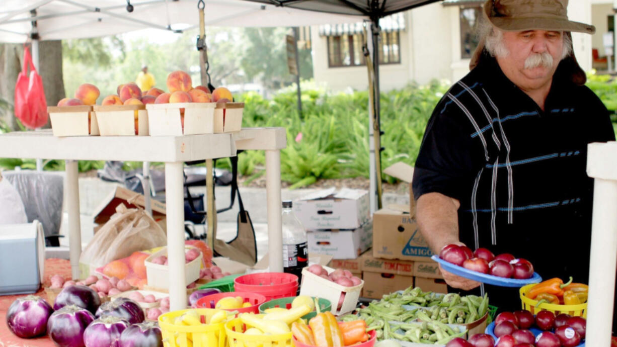 A customer checks out produce at a farmers market. Since the pandemic, farmers in Ohio are looking  for new ways to sell their meat and produce.