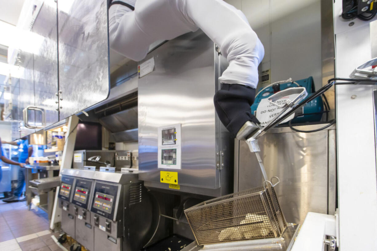 """Miso Robotics' Flippy ROAR grabs a basket of cheese sticks for the fryer at a White Castle in Merrillville, Ind., on July 6, 2021. This location is testing """"Flippy ROAR,"""" a robotic fryer by Miso Robotics and an automated voice that takes orders at the drive-thru."""