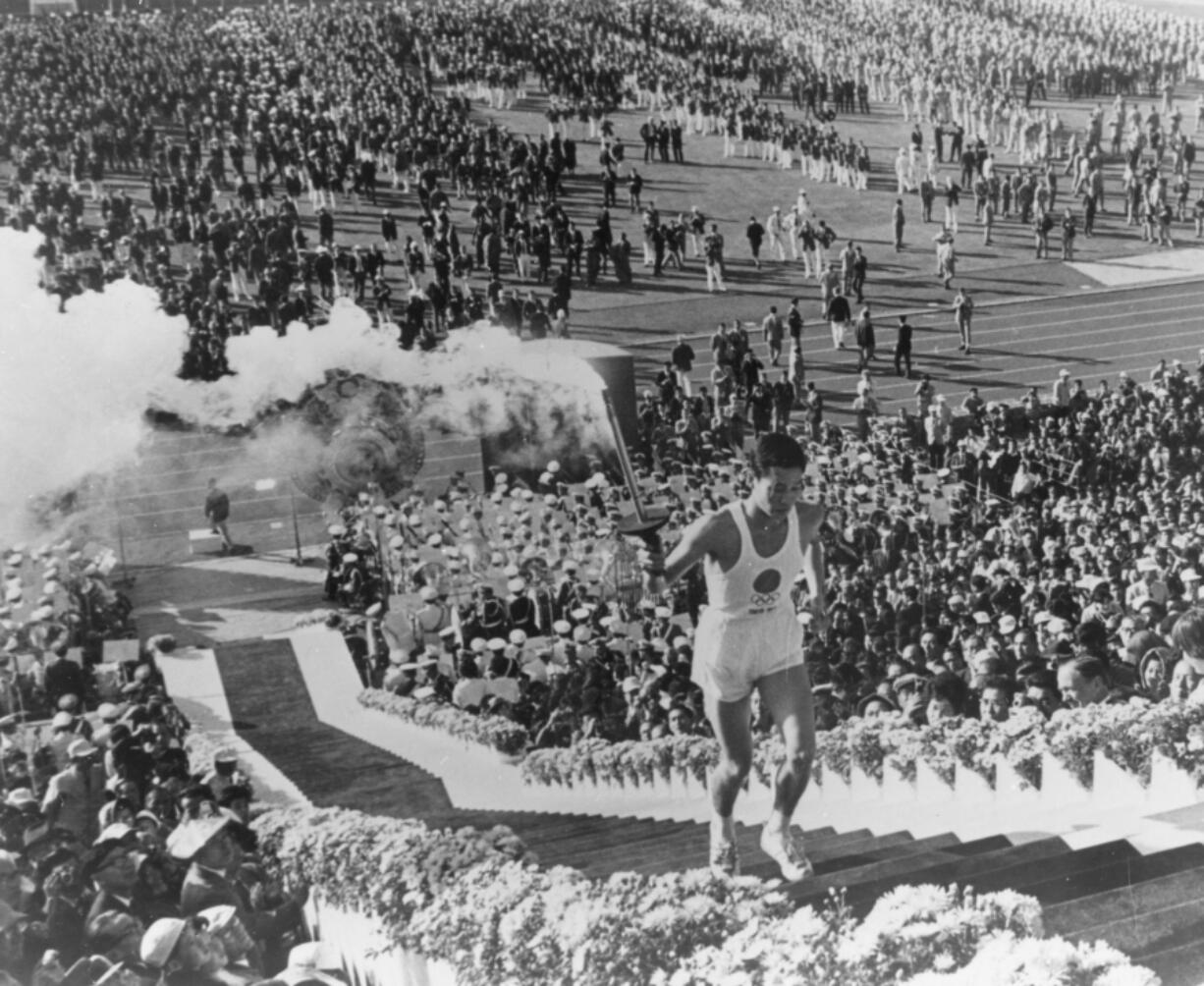 Yoshinori Sakai, born in Hiroshima on the day the first atomic bomb devastated the city, carries the torch up the stairs to light the cauldron during the opening ceremony for the 1964 Tokyo Summer Olympic Games.