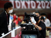 A TV host cameraman checks his camera Wednesday inside the Nippon Budokan venue for judo and karate events during the Tokyo 2020 Olympic Games in Tokyo.