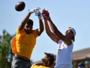 Players from Kelso and Sandy (Ore.) high school leap for a ball Saturday during the Rumble at the River 7-on-7 football tournament at Union High School.