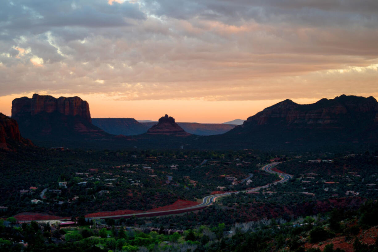 Overcast skies as the sun sets over the Verde Valley region, as people watch the sunset from atop of the summit of the Airport Mesa Loop Trail on Monday, April 20, 2020 in Sedona, Arizona.