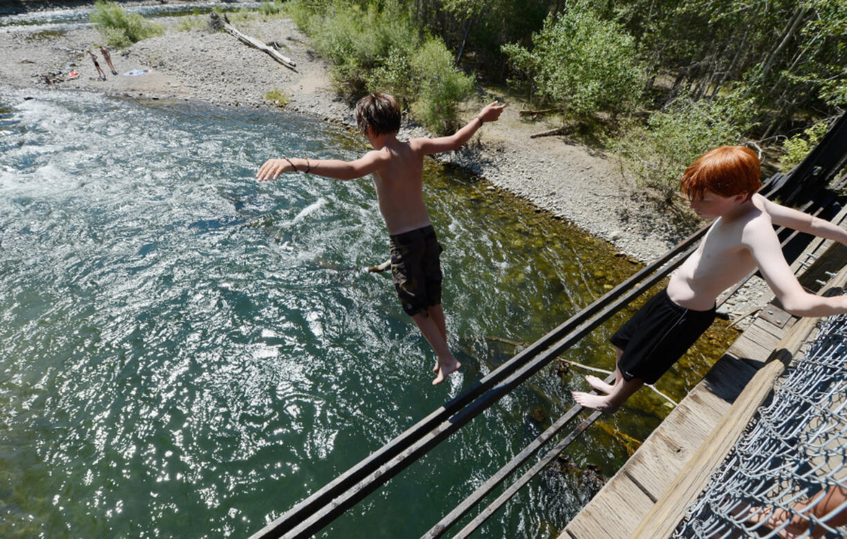 Young swimmers cool off by jumping into the Big Wood River from an old train bridge in Sun Valley, Idaho, on July 9, 2012. A surprise drought has been accompanied by an extreme heat wave in parts of Idaho this summer.