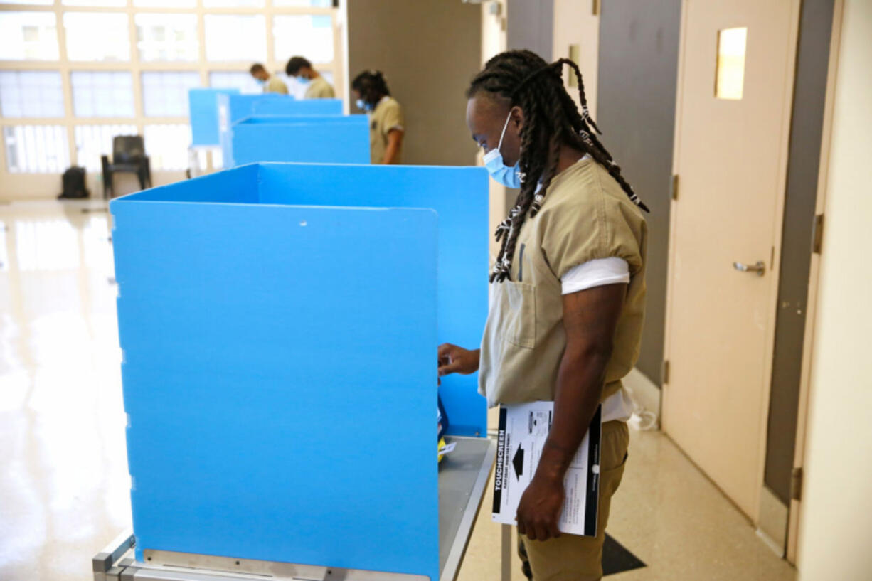 A Cook County jail detainee uses a touch screen to cast his votes at a polling place in the facility set up for early voting on October 17, 2020 in Chicago, Illinois.