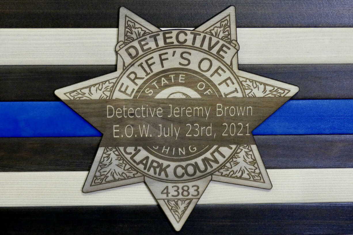 A memorial for Clark County sheriff's Detective Jeremy Brown depicts a mourning band over a badge with his end of watch date.