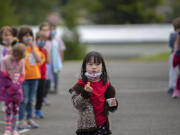 Kindergartner Tiffany Chang briefly drops her mask to enjoy a socially-distanced snack after recess at Eisenhower Elementary School in May. All students and staff will need to wear masks when the school year starts.
