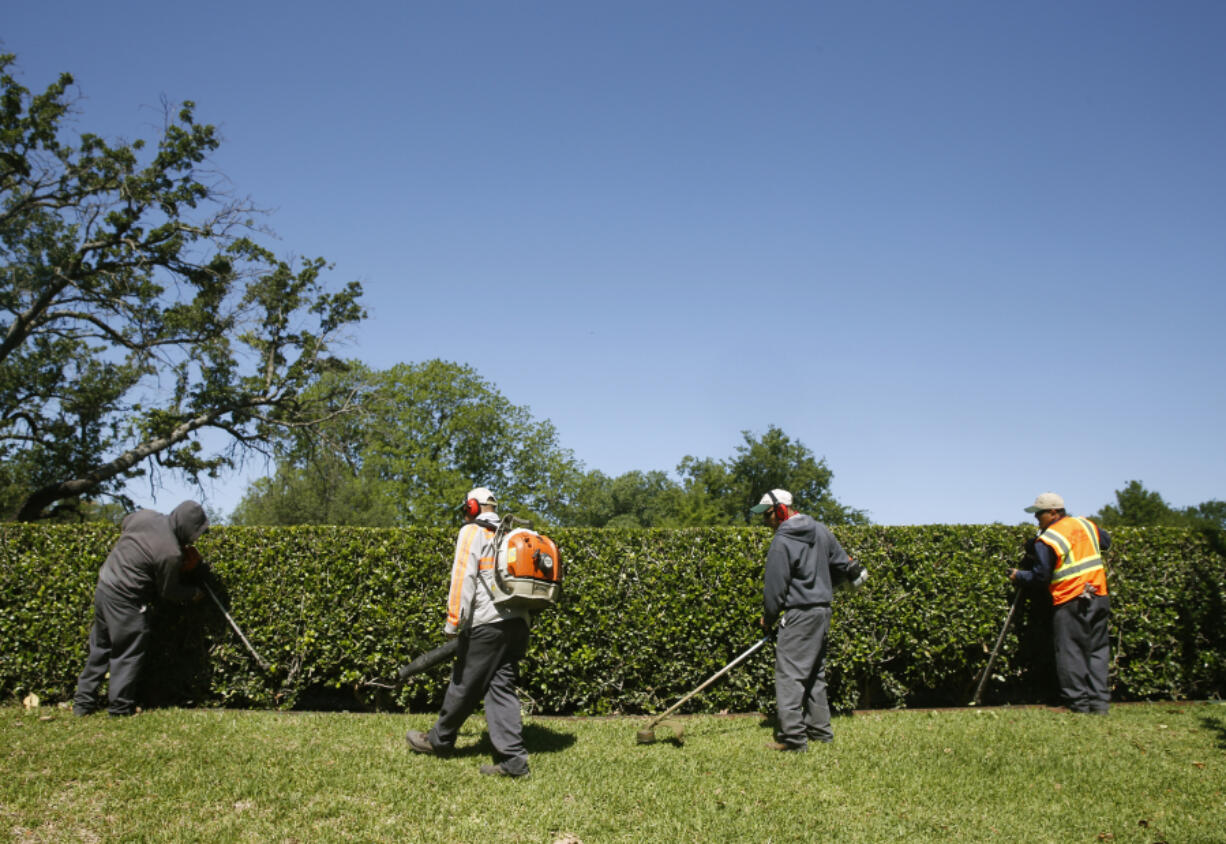 Workers trim up the entryway to a neighborhood in Lake Forest in Dallas on May 4, 2017. Companies use H-2B visas to recruit seasonal workers for landscaping, food preparation, construction and other manual work. In 2019, Texas led all states with over 16,000 positions certified for H-2B visas.
