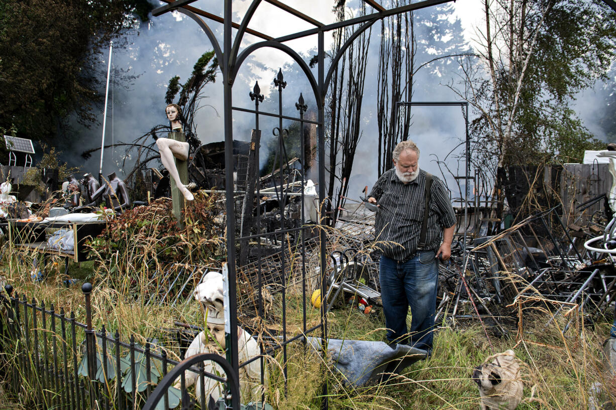 Property owner Steve Slocum surveys the fire scene with his dog, Frank, after a former church and the house next door burned down in an early morning blaze in Battle Ground on Monday, July 5, 2021. Officials said the fire could've been sparked by fireworks and no injuries were reported.