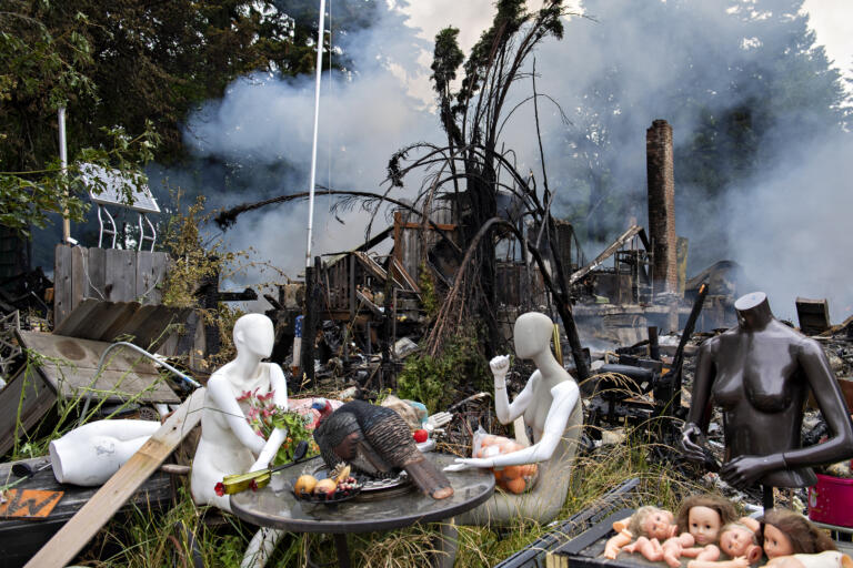 Mannequins sit down to a turkey dinner as the property behind them smolders after an early morning fire on Northeast 92nd Avenue in Battle Ground on Monday morning, July 5, 2021.
