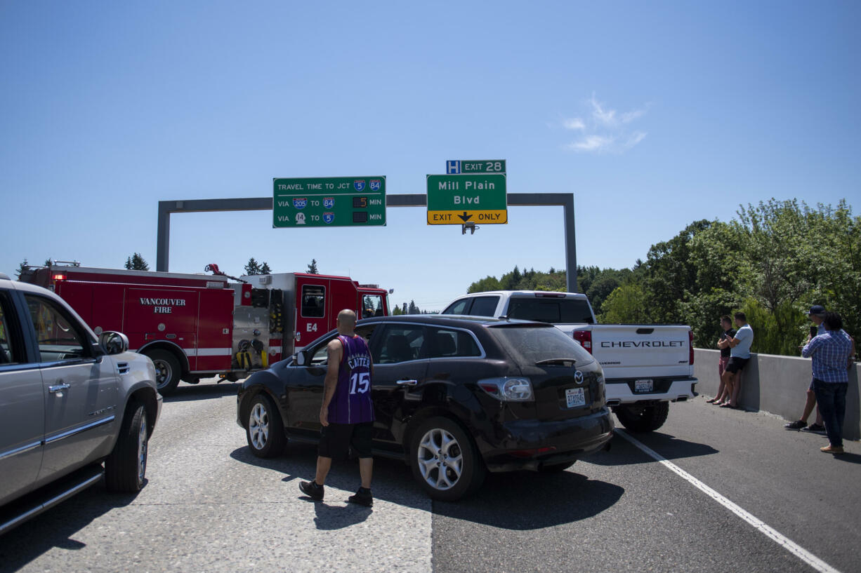 Stuck motorists survey the scene as they gather in the southbound Interstate 205 near the Mill Plain Boulevard exit on Friday afternoon, July 9, 2021.
