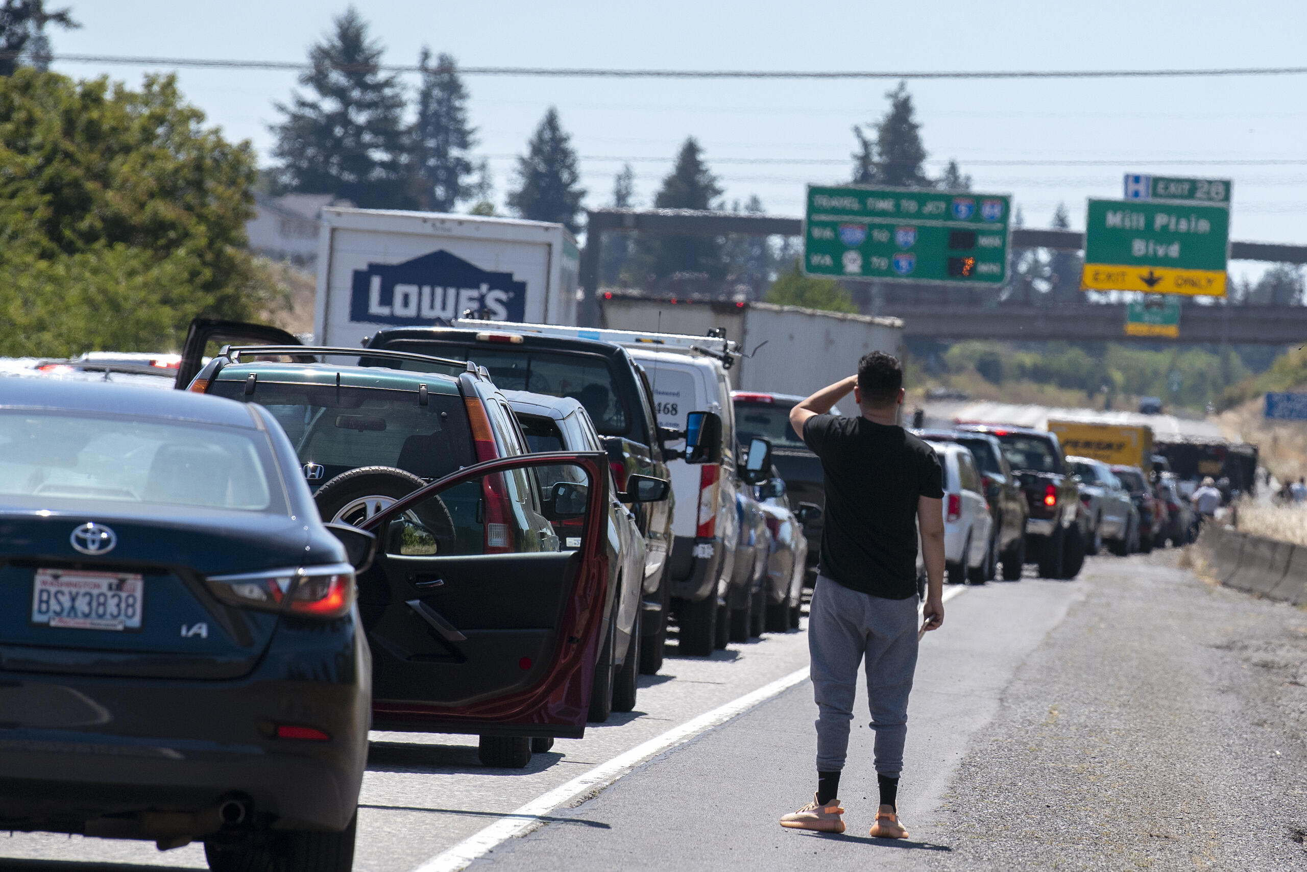 A motorist stuck in the southbound lanes of Interstate 205 near the Mill Plain Boulevard exit checks out the accident scene on Friday afternoon, July 9, 2021.