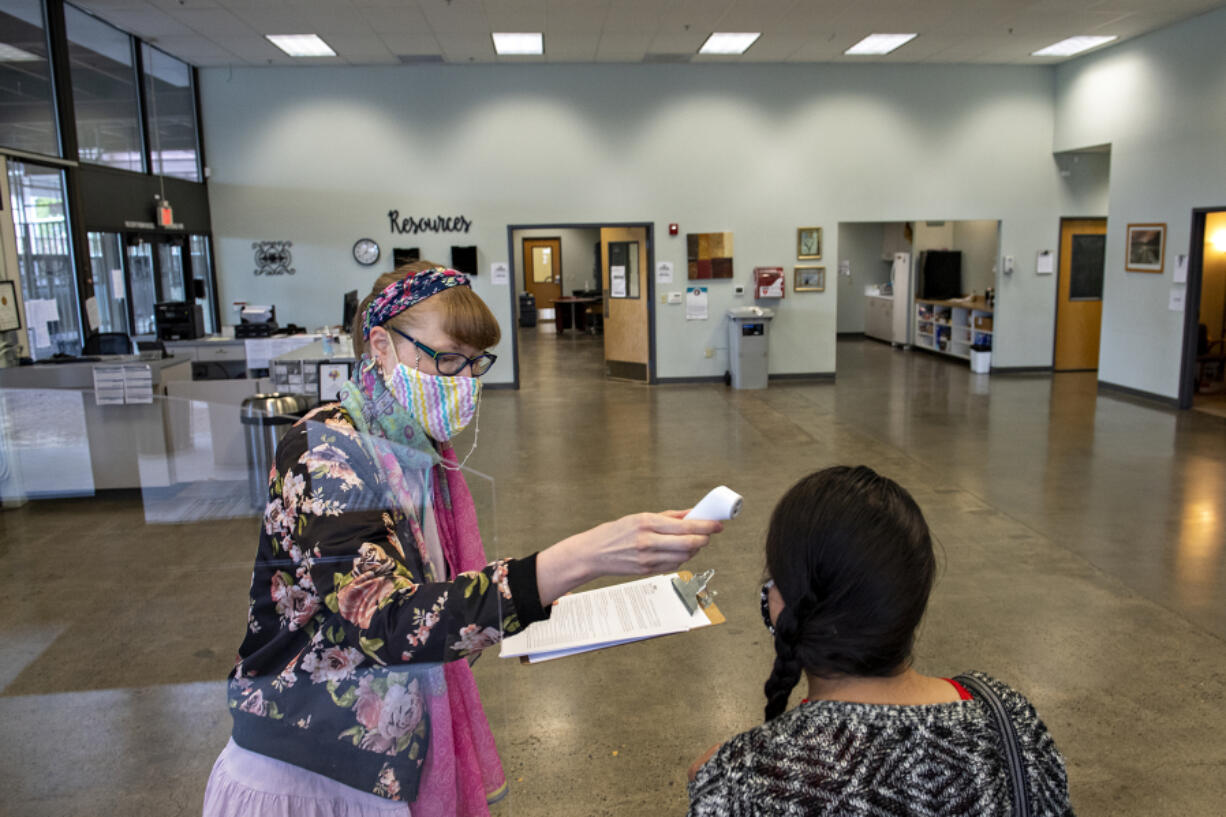 Rachel Korf, left, behavioral health receptionist for SeaMar Community Health Centers, takes the temperature of Prisli Maldonado, maternity support and community health worker, as she checks in for work at the former location of the Vancouver Navigation Center on Thursday morning, July 8, 2021.