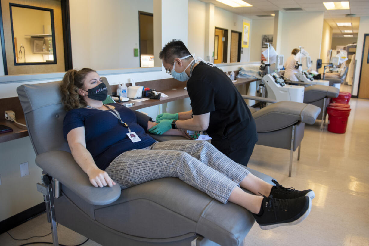 Lauren Reagan, center, the mother of the late Declan Reagan, chats with colleague Tin Nguyen as she donates blood at Bloodworks Northwest Vancouver Donor Center on June 25. Bloodworks and blood donations helped Declan live five months longer than expected. At top, Declan plays in his dad's police cruiser at the Washougal Police Department on Sept. 5, 2017.