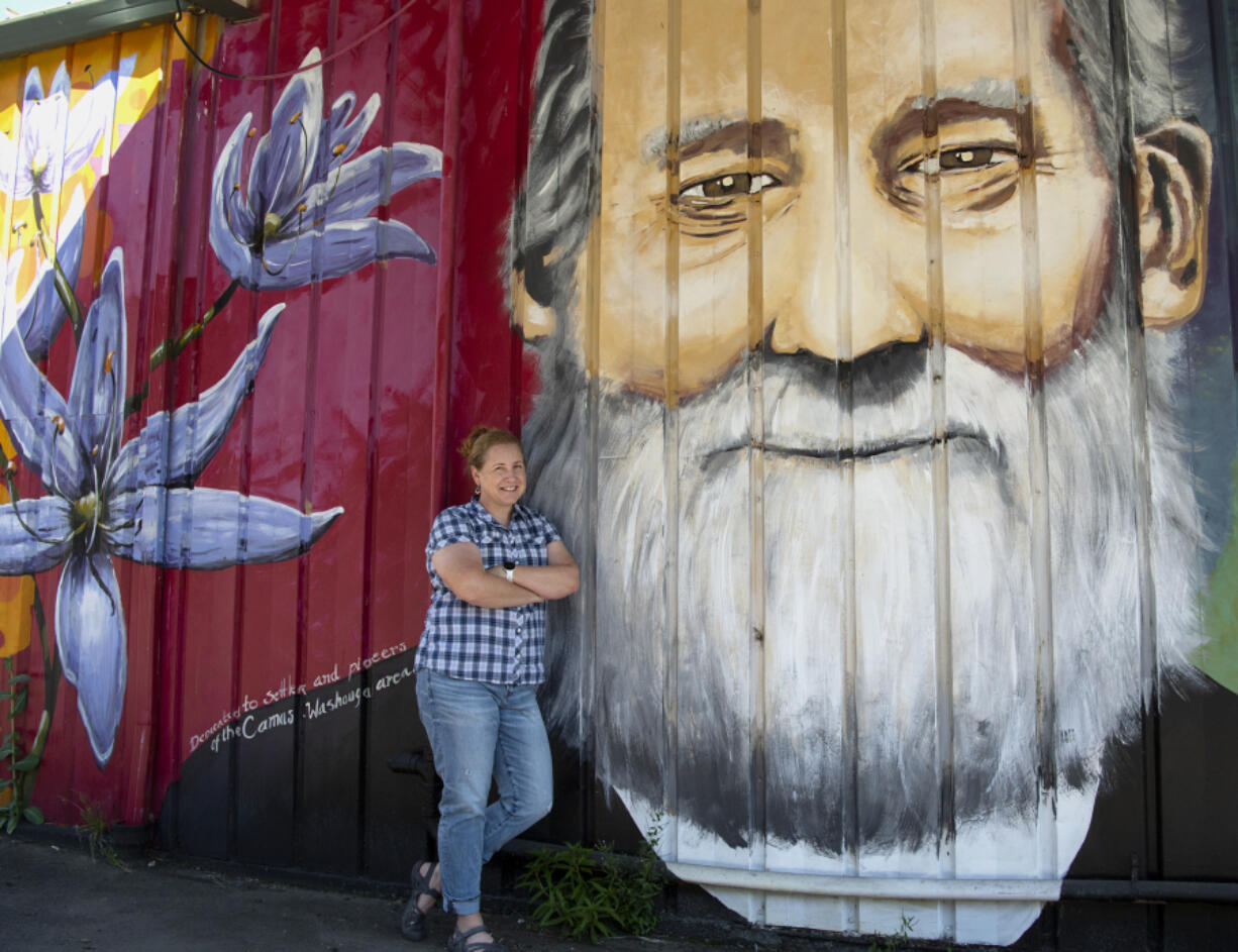 """Descendant Anne Christie poses next to the face of Richard Ough, the founder of Washougal and her triple-great grandfather. """"We love it,"""" Christie said. """"This is my dad's family."""