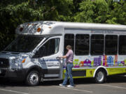 Michael Kelly, transportation services manager for Community in Motion, steps into one of two newly decorated vehicles Thursday afternoon.