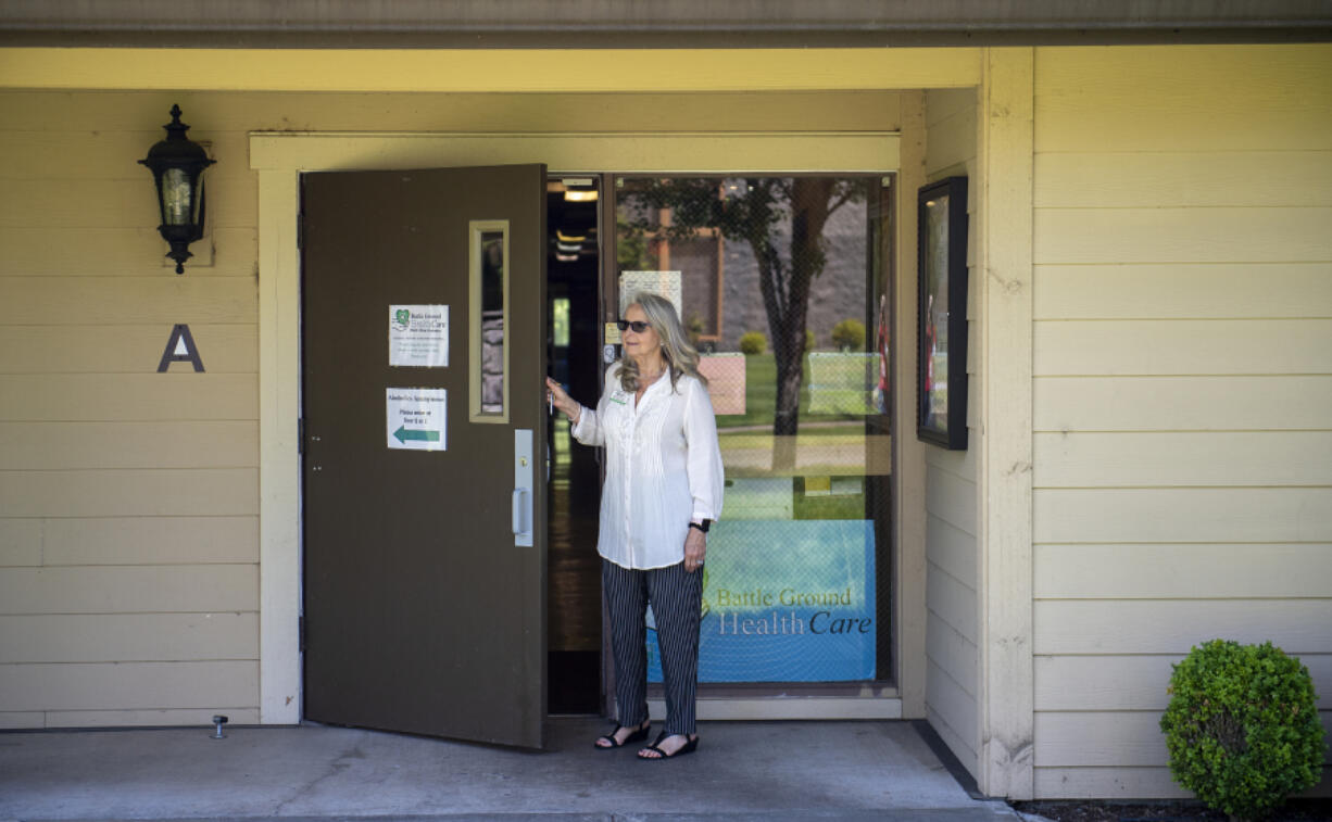 Executive director Sue Neal of Battle Ground Health Care looks out the front door of the current facility in Meadow Glad. The clinic was recently awarded a $1.1 million community development block grant to purchase a new, bigger building in a more visible location in Battle Ground.