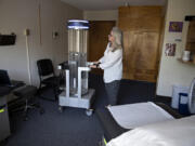 Sue Neal, executive director of Battle Ground HealthCare, looks over a rapid disinfector ultraviolet light sterilizer that helps fight COVID-19. The free clinic provides a range of health care services, which will be expanded at the new location.