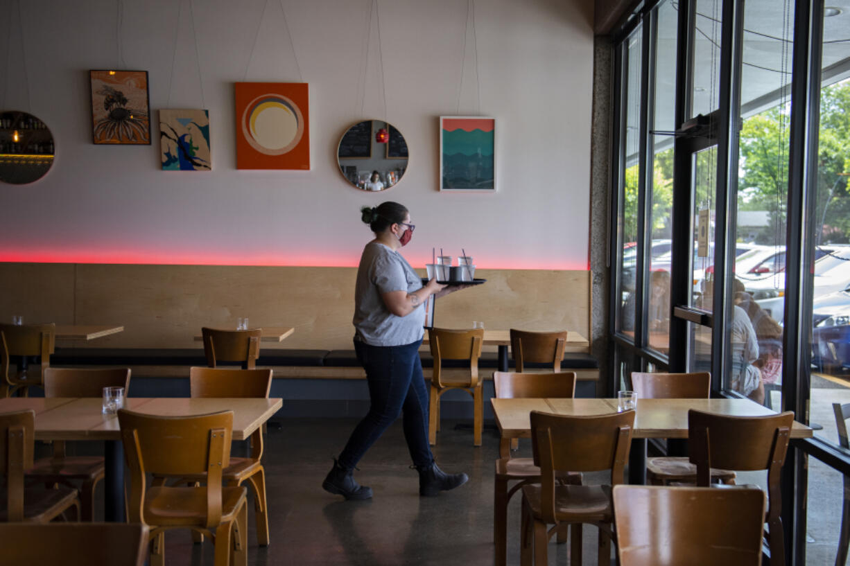 Server Bethany Fischer walks through the dining room at Rally Pizza that is now open for those wanting to eat inside, on Friday afternoon.