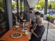 Thea Coleman of Portland, from left, looks on as server Bethany Fischer serves up lunch while joined by Isabella Coleman, 15, and Mea Agee of Vancouver while dining outside at Rally Pizza on Friday afternoon. The dining room is now also open for customers.