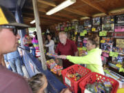 Les Clifton, left, and Arieonna Falander, right, help Yacolt customers buy fireworks to celebrate the Fourth of July, despite fireworks being banned everywhere else in Clark County for their fire risk. Clifton anticipates this year being the most successful year of sales.
