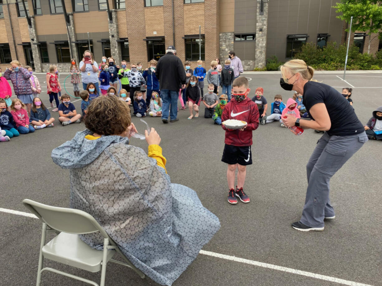 WASHOUGAL:  Columbia River Gorge Elementary School first-grader Jase Kenyon gets ready to smash Principal Tracey MacLachlan as teacher Jessica Warta observed.
