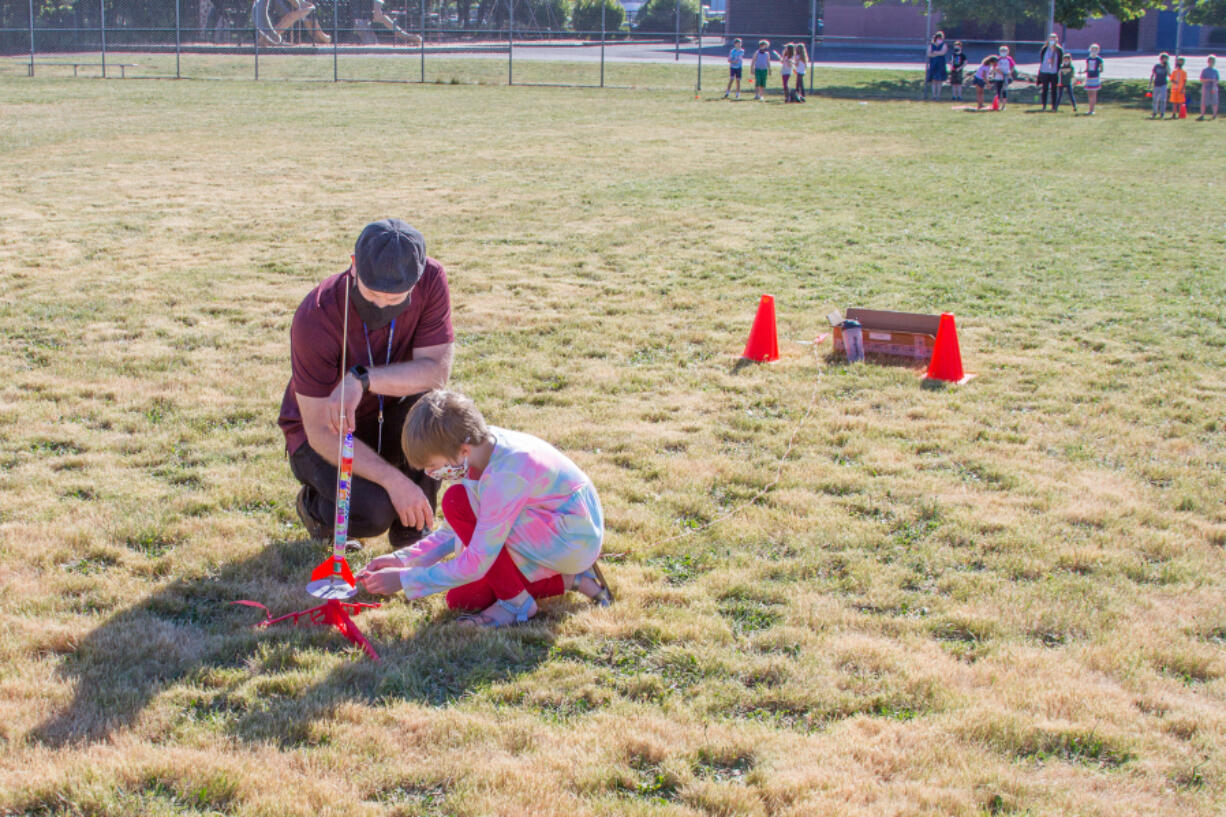 WOODLAND: Brian Peterson, third-grade teacher, helps a student prepare a rocket for launch.