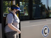 Vancouver resident Rachael Okerlund steps off a C-Tran bus wearing a face covering on Friday at the Vancouver Mall Transit Center. Face coverings remain a requirement on Vancouver public transit in accordance with CDC rules.