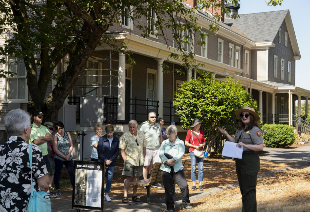 Guests listen to National Park Service curator Meagan Huff talk about the work immigrants performed at Vancouver Barracks in the 1880s. The former Infantry Barracks in the background now serves as headquarters of the Gifford Pinchot National Forest.