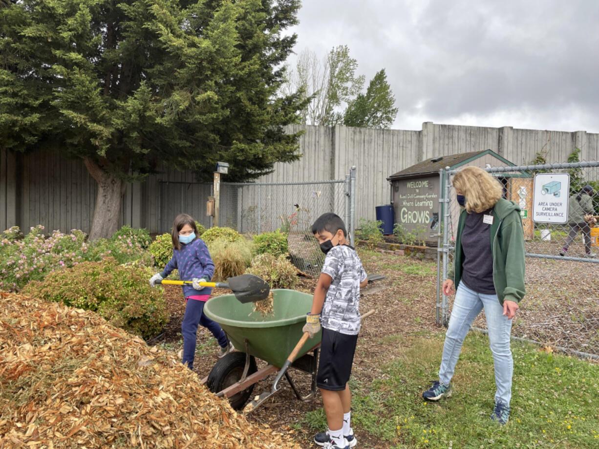 HAZEL DELL: Master Gardener Denise Jones helped Pearl Harvet and Axel Reteguin-Vargas shovel bark into the wheelbarrow to spread on the garden paths to keep weeds under control.
