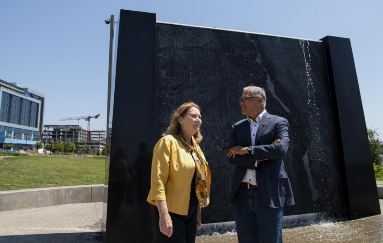 Vancouver Mayor Anne McEnerny-Ogle and Gov. Jay Inslee survey The Waterfront Vancouver while standing in front of an interactive sculpture that depicts the topography of the Columbia River on Tuesday. Inslee toured the waterfront with the mayor before meeting with local small-business owners.