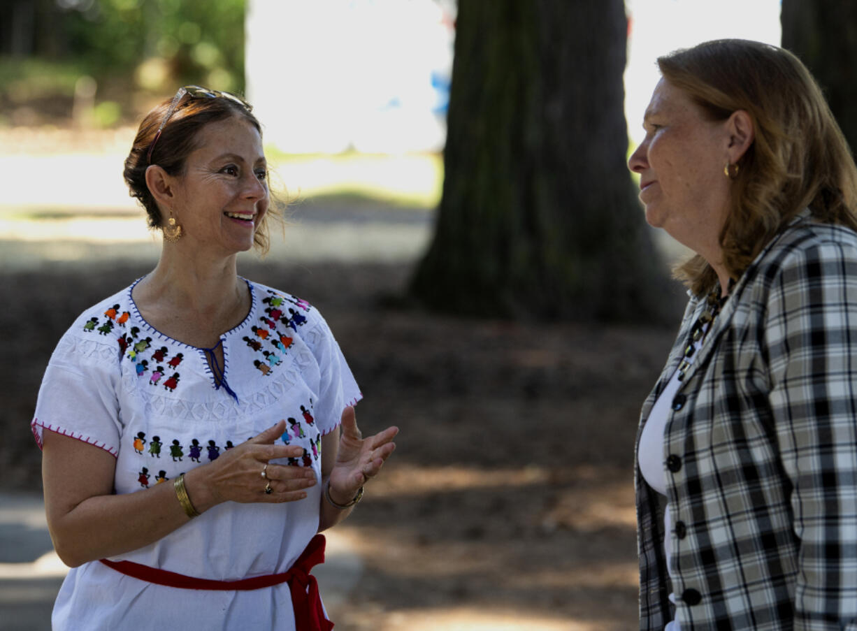 """Anna Cruz speaks with Vancouver mayor Anne McEnerny-Ogle at the Espacio de Arte in El Parque on Saturday at Evergreen Park in Vancouver. Cruz, as part of Vancouver Ballet Folkorico and in partnership with Fourth Plain Forward and Artstra, hosts the """"Art in the Park"""" event twice a month."""