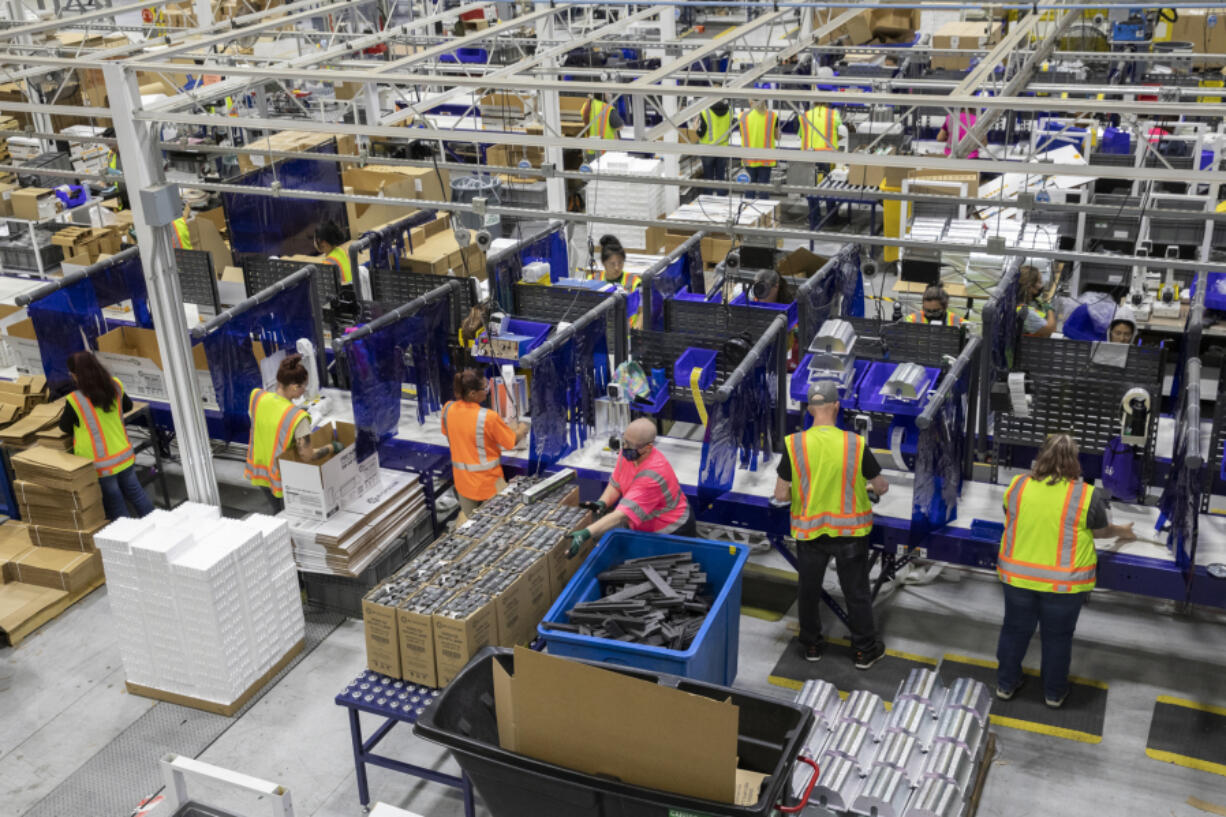 Workers assemble products and packaging on the manufacturing floor at Hawthorne Gardening Company in Vancouver on Wednesday. The company, a subsidiary of ScottsMiracle-Gro, has seen a sustained boom in demand for its hydroponic equipment since the COVID-19 pandemic began.