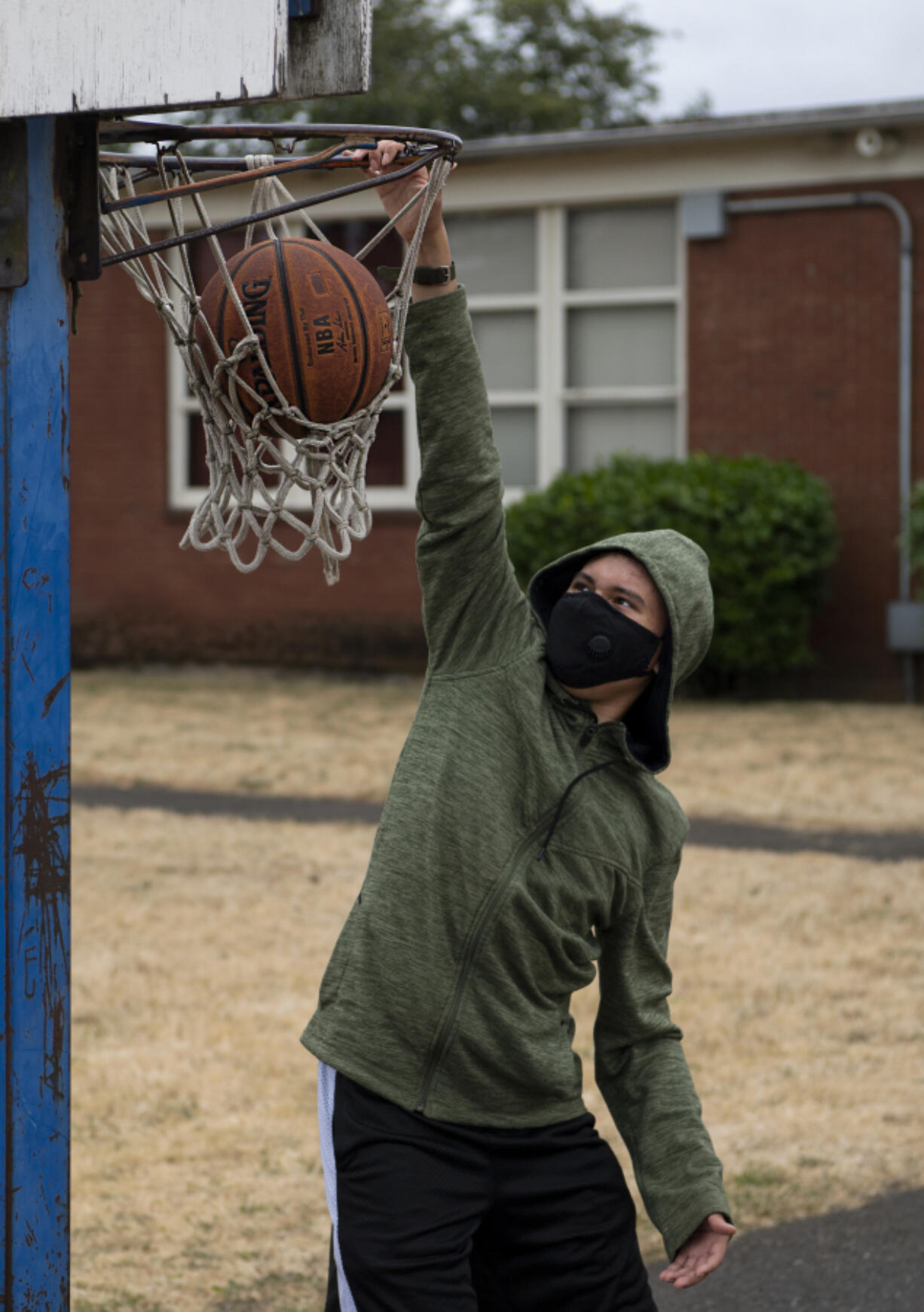 Roane Vanderley, 18, dunks a basketball at an Access to Recreation camp on Tuesday.