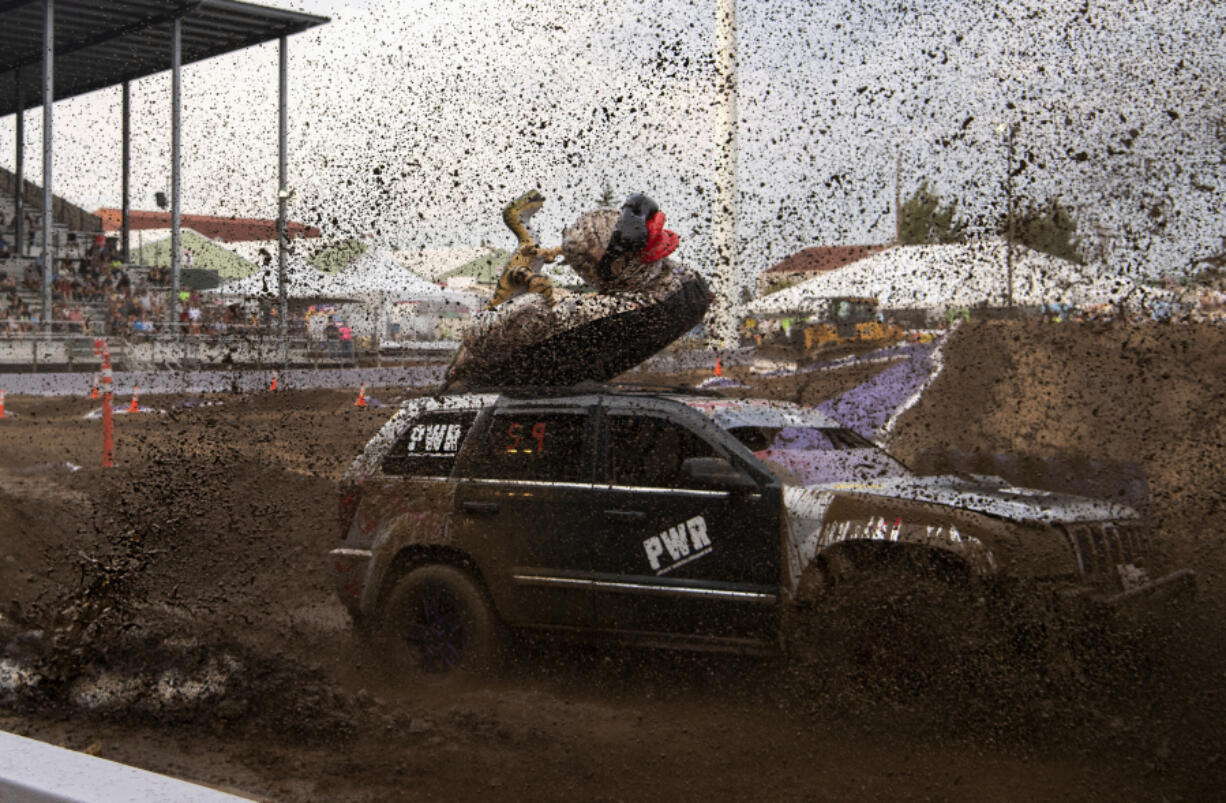 Vancouver's Chess Archibald powers his vehicle, including the inflatable duck and dinosaur strapped to its roof, through the mud during Friday's Tuff Trucks event at the Clark County Event Center at the Fairgrounds. Tuff Trucks was the first event in the Family Fun Series, which continues through Aug. 15.