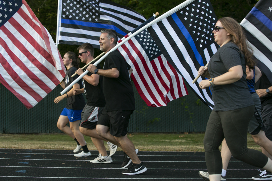 """Jason Hattrick, center, CEO of Kindness 911 and organizer of the """"Honor Mile"""" event to memorialize Detective Jeremy Brown, runs alongside other flag holders at Alki Middle School on Wednesday. Brown, a 15-year veteran of the sheriff's office, was shot and killed in the line of duty in east Vancouver Friday night."""