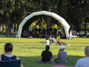 Visitors lounge in the grass to watch the Minidoka Swing Band on Thursday at a new park at Northeast 52nd Street and 137th Avenue in Vancouver's North Image neighborhood. Residents will be able to vote on the new park's name.