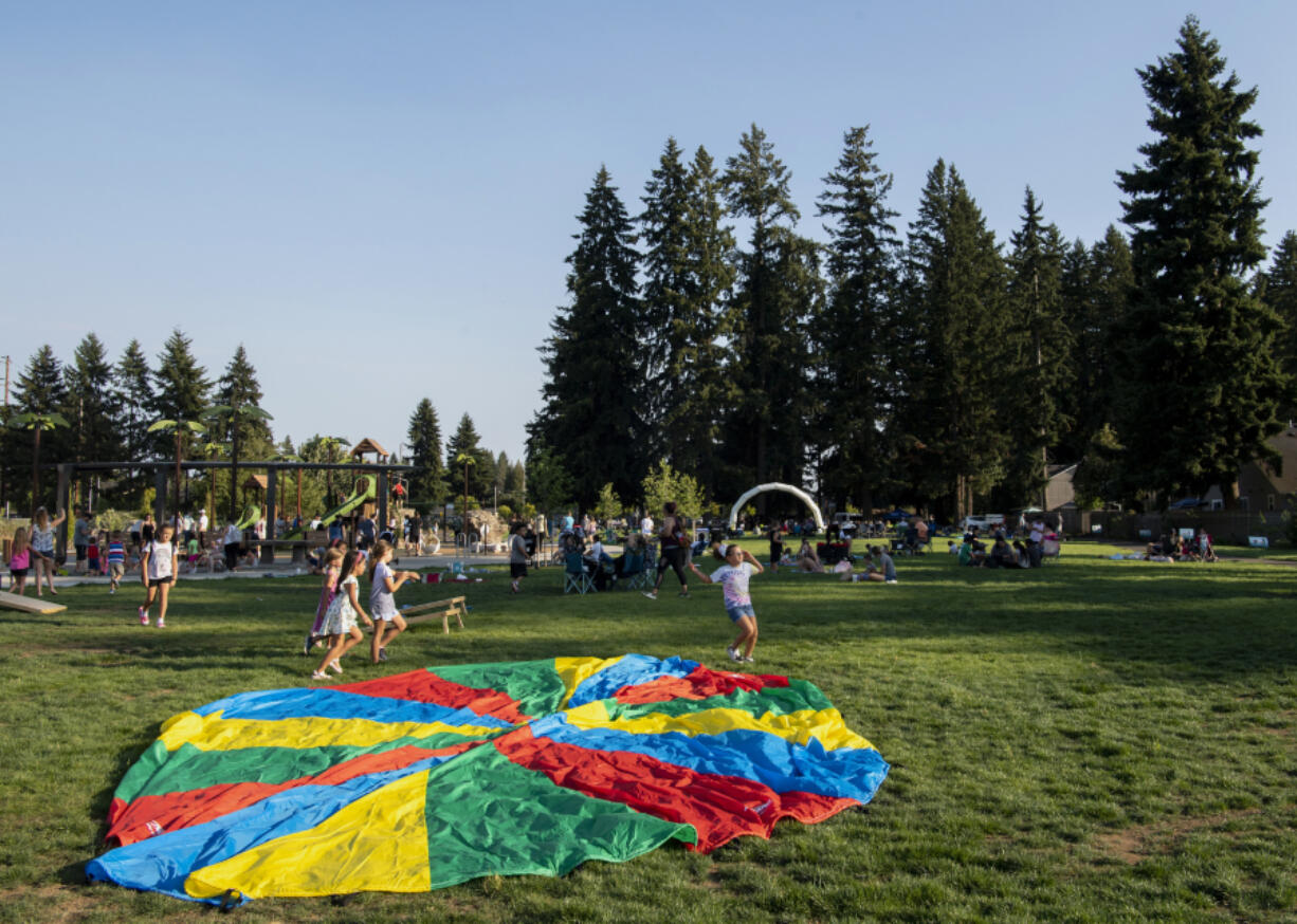 At right, kids run through a field Thursd ay at a park in Vancouver's North Image neighborhood. The new park at Northeast 52nd Street and 137th Avenue hosted Party in the Parks, which featured live music, games and informative booths.