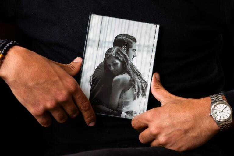 Abraham Dairi holds a photograph of him and his wife, Holly Deierling, while sitting at his home in Seattle's Montlake neighborhood on July 1, 2021. (Matt M.