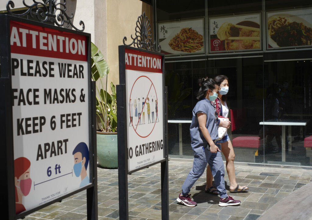 FILE - In this June 11, 2021, file photo, customers wear face masks in an outdoor mall with closed business amid the COVID-19 pandemic in Los Angeles. The latest alarming coronavirus variant, the delta variant, is exploiting low global vaccination rates and a rush to ease pandemic restrictions, adding new urgency to the drive to get more shots in arms and slow its supercharged spread.
