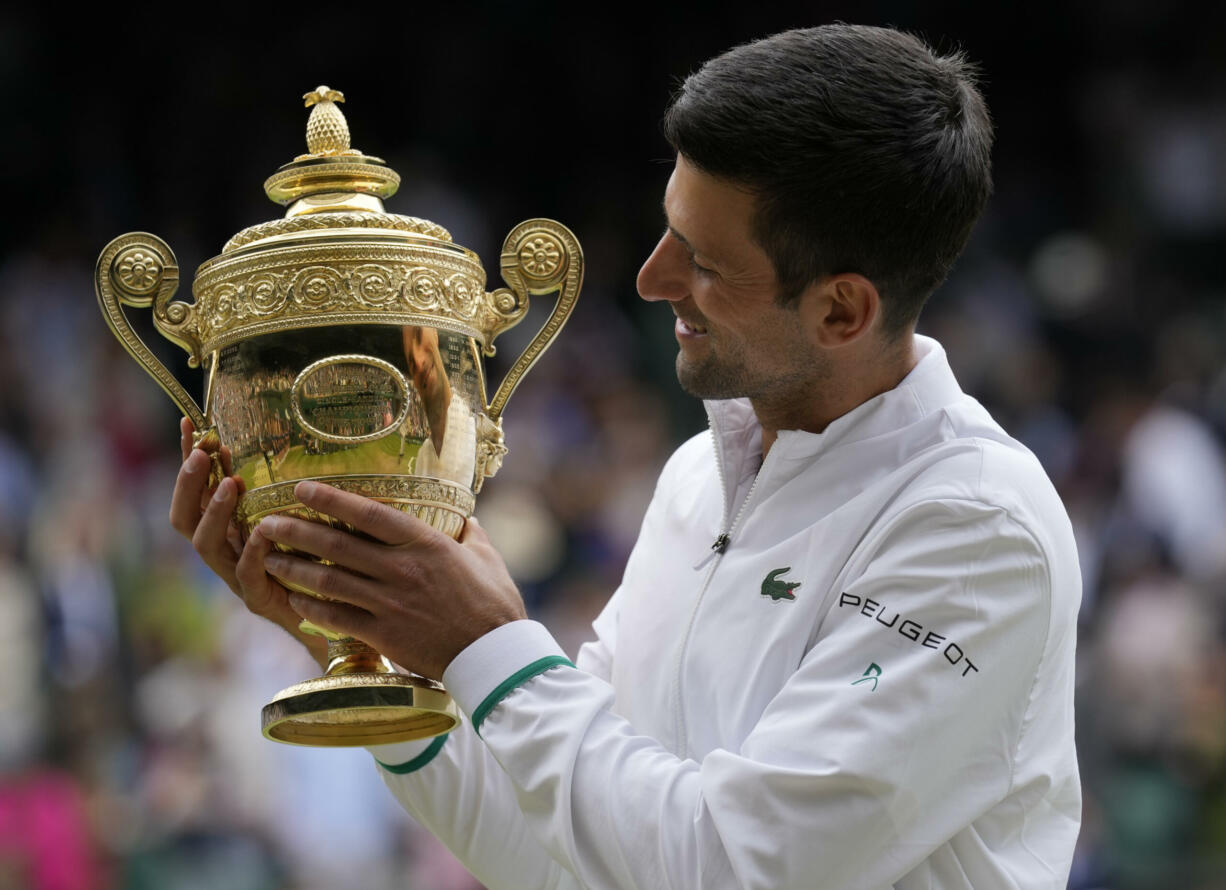 Serbia's Novak Djokovic holds the winners trophy as he poses for photographers after he defeated Italy's Matteo Berrettini in the men's singles final on day thirteen of the Wimbledon Tennis Championships in London, Sunday, July 11, 2021.