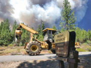 In this photo provided by the Bootleg Fire Incident Command, the Bootleg Fire burns behind heavy equipment at the Mitchell Monument in southern Oregon on Saturday, July 17, 2021. The 569-square-mile (1,474 square kilometers) Bootleg Fire is burning 300 miles (483 kilometers) southeast of Portland in and around the Fremont-Winema National Forest, a vast expanse of old-growth forest, lakes and wildlife refuges.