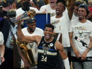 Milwaukee Bucks forward Giannis Antetokounmpo (34) reads with the championship trophy after defeating the Phoenix Suns in Game 6 of basketball's NBA Finals in Milwaukee, Tuesday, July 20, 2021. The Bucks won 105-98.